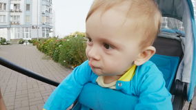 Slow motion closeup footage of cute baby in pram shaking head and making faces stock footage