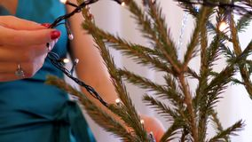 Slow motion closeup girl puts garland on Christmas tree. Slow motion closeup girl in green dress puts garland on Christmas tree by manicured hand at home stock footage