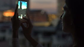 Slow motion of Closeup woman taking photo of cityscape view with smartphone in bar rooftop terrace at night stock footage