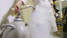 Slow Motion Woman Controls Lever Discharging Liquid Nitrogen stock video