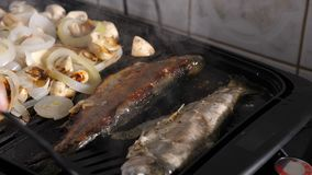 Cook hands turn a fish on the grill. Slow motion of cook hands turn a fish on the grill stock video