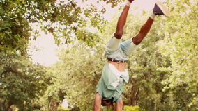 In slow motion cool young break dancer doing back flip in the park. On a sunny day stock video footage