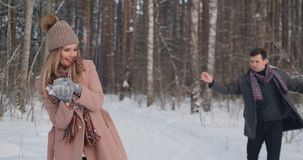 Slow motion - Couple snowball fighting in a field. They end their fight on a good terms with a high five. Slow motion - Couple snowball fighting in a field stock video