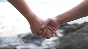Slow motion couple Women and men Join hands on the beach to feel warm. Romantic and loving  .as background Valentine concept with. Copy spaces for your text or stock video footage