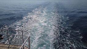 Crane shot. White foam trail behind motor boat or ship. Water splatter behind ship stern