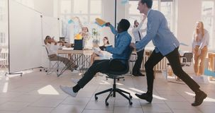 Slow motion crazy fun young black businessman riding office chair, celebrating success with team throwing paper in air.
