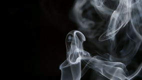 SLOW MOTION: Curve smoke lifts up on a dark background stock footage