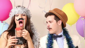 Slow motion of cute couple having fun in party photo booth. Slow motion of cute young couple having fun in party photo booth stock video