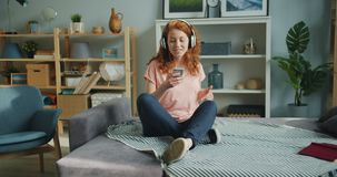 Slow motion of cute girl listening to music dancing and using smartphone at home. Slow motion of cute girl listening to music in headphones dancing and using stock video