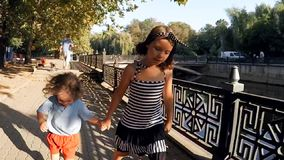 SLOW MOTION. Cute kids brother and sister walking by the river in the city park . stock video footage