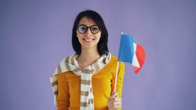 Slow motion of cute young brunette in glasses holding French flag smiling. Slow motion of cute young brunette in stylish glasses holding French national flag stock footage