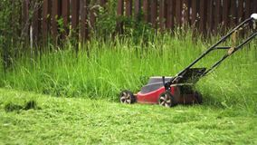 Slow motion cutting grass with electric lawn mower stock video footage