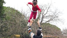 Slow motion of father throwing his adorable daughter in the air stock video footage
