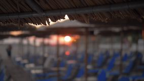 Beach with chaise longues and straw umbrellas at sunset. Slow motion defocused shot of few people at the beach at sunset. View to empty chaise-longues from under stock video footage