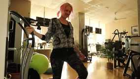 Legs warm up. Slow motion detail on fit woman warming up, training leg exercise on vibration plate. Modern gym defocused background. Female athlete preparing stock video