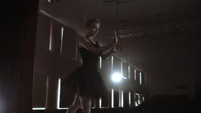 Slow motion: Diligent young graceful ballerina dancing elements of classical ballet in the dark with light and smoke on. The background. Beautiful young stock video