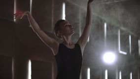Slow motion: Diligent young graceful ballerina dancing elements of classical ballet in the dark with light and smoke on. The background. Beautiful young stock footage