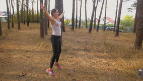 Slow motion dolly shot of sexy young woman warming up and exercising at forest stock video footage