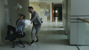 Slow motion dolly shot of two crazy businessmen riding office chair and throwing papers up while having fun in lobby of. Modern business center indoors stock video