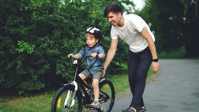 Slow motion of excited boy riding bicycle and laughing while his careful father is helping him holding bike and teaching