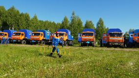 Fire brigade man carries ladder past vehicles on training field. Slow motion fire brigade man in outfit carries ladder past large blue-orange vehicles on stock footage