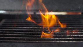 SLOW MOTION: Fire is burning and heats barbecue grill.  stock video footage