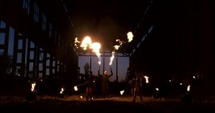 Slow motion: Fire show in the hangar show three female artist and a man with flamethrowers. stock footage