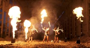 Slow motion: Fire show in the hangar show three female artist and a man with flamethrowers. stock video