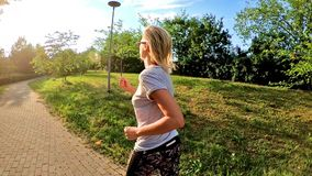 Woman jogging outdoor. SLOW MOTION fit blonde woman running in slow motion in the sun at sunset. Fit woman jogging on a city park street. outdoor cardio jogging stock footage