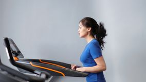 Slow motion fitness Asian woman doing cardio running on treadmill at gym or home medium shot