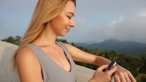 Slow motion fitness trainer girl testing smartwatch on balcony of hotel stock video footage
