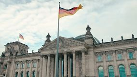Slow Motion The flag of Germany against the background of the building of the Bundestag- parliament in the center of the. Capital Berlin. Against the background stock footage