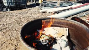 Trash burning in barrel. Slow motion flames of burning trash in metal barrel stock video
