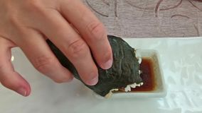 Temaki Cone in soy sauce. SLOW MOTION: focused hand putting a California Temaki cone with rice, avocado and seaweed, in soy sauce bowl. Japanese fusion food stock video footage