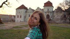 Slow motion follow me - happy young woman pulling guy`s hand against the background of an old castle stock video