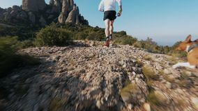 Trail running in mountains. Slow motion following shot of professional athlete or trail runner during race, workout or training for marathon in epic mountains or stock footage