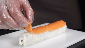 Slow motion food concept. Professional sushi chef preparing delicious roll at commercial kitchen. Cook puts sliced stock video