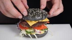 Slow motion food cooking. Hands preparing a hamburger. Close up view of preparing a beef hamburger at the street food stock video footage