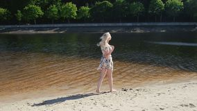 Slow motion video of beautiful young woman in short dress walking by the river. Slow motion footage of beautiful young woman in short dress walking by the river stock footage