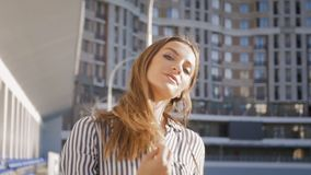 Slow motion video of beautiful young woman walking on street and turning around while looking in camera. Slow motion footage of beautiful young woman walking on stock video footage