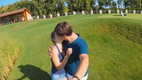 Slow motion footage from camera on selfie stick of happy young couple kissing at park. Slow motion footage from camera on selfie stick of happy couple kissing at stock video