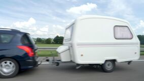 Slow motion footage defocused view of Peugeot car and RV trailer