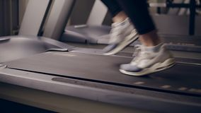 Slow motion footage of female legs in fancy sneakers running on treadmill. Slow motion footage of female legs in fancy sneakers running on treadmill stock footage