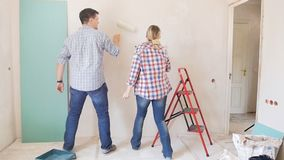Slow motion footage of happy cheerful couple dancing while painting walls with paint roller at their new apartment under. Slow motion video of happy cheerful stock video
