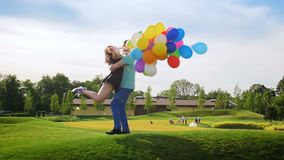 Slow motion video of happy cheerful young couple holding colorful balloons and having fun at park. Slow motion footage of happy cheerful young couple holding stock footage