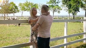 Slow motion video of happy young couple hugging near paddock at farm stock video footage