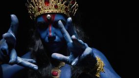 Kali wearing gold jewelry with red rubies is moving her hands, close up