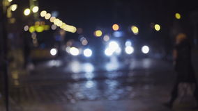 Slow motion footage of night traffic in a city center. Pedestrians cross the street on a crosswalk. Blurred image of. Slow motion footage of  night traffic in a stock footage