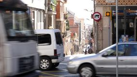 Slow motion footage of pedestrians cars on a calm street. Barcelona, Spain - Circa 2019: Slow motion footage of pedestrians cars on a calm street in Barcelona stock video footage