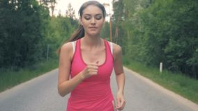 Slow motion footage of a pretty lady jogging along the alley. Healthy slim young sportswoman running. stock video footage